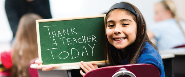 Student holding a chalkboard that says thank a teacher today.